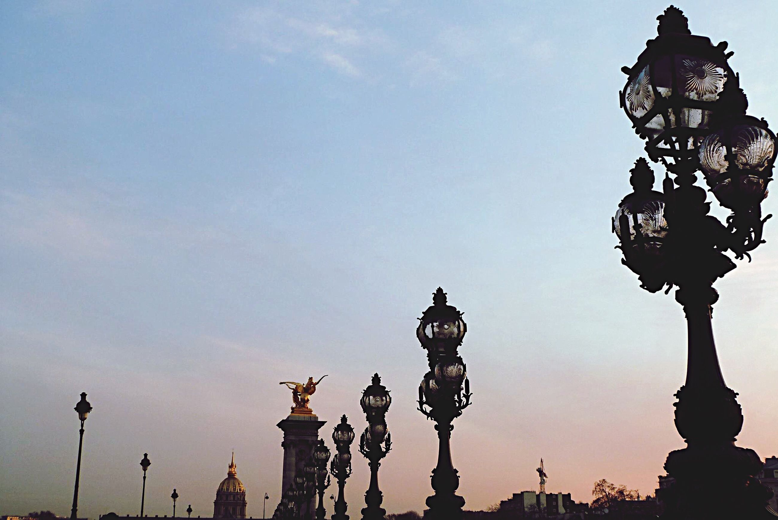 statue, low angle view, religion, art and craft, sculpture, street light, art, architecture, human representation, spirituality, lighting equipment, place of worship, high section, sky, creativity, travel destinations, lamp post, cloud, outdoors, tourism, history, famous place, no people