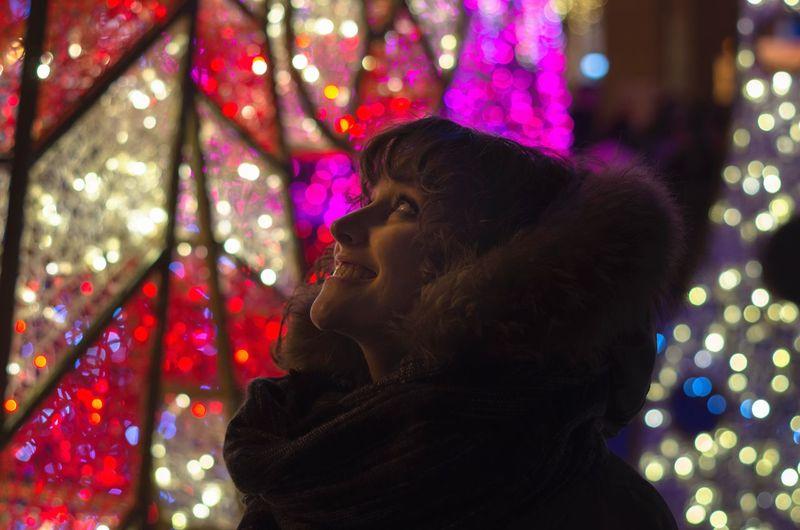 Happy Beautiful Woman Wearing Fur Clothing Against Illuminated Decoration