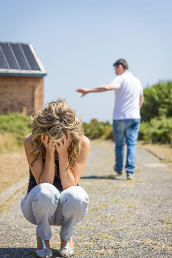 Rear view of couple sitting against clear sky