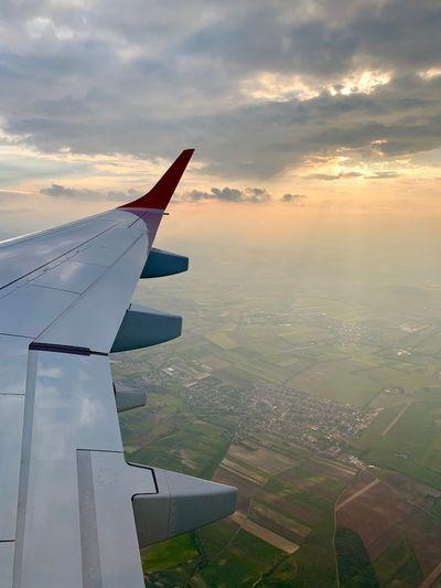 Airplane flying over landscape against sky