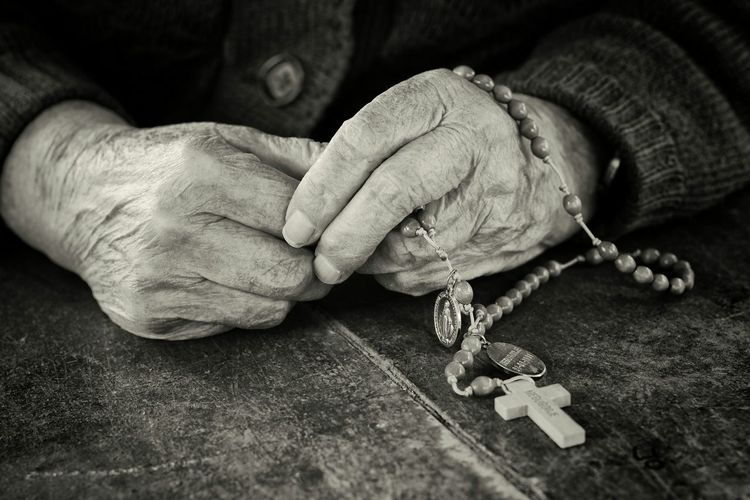 Close-up of hands holding rosary at table