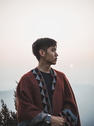 Young man looking away against sky during sunset