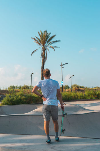 Rear view of man standing by palm trees against sky