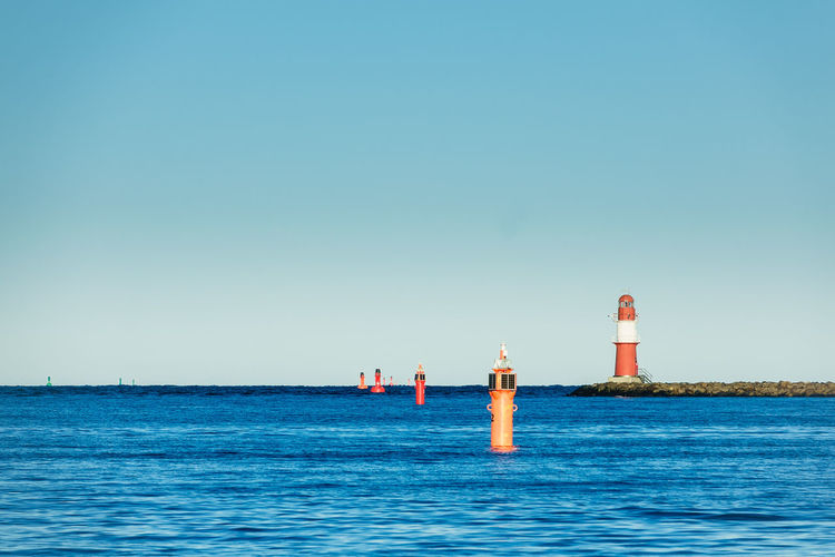 Lighthouse by sea against clear sky