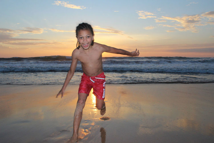 Portrait Of Smiling Shirtless Boy Running On Sea Shore Against Sky During Sunset