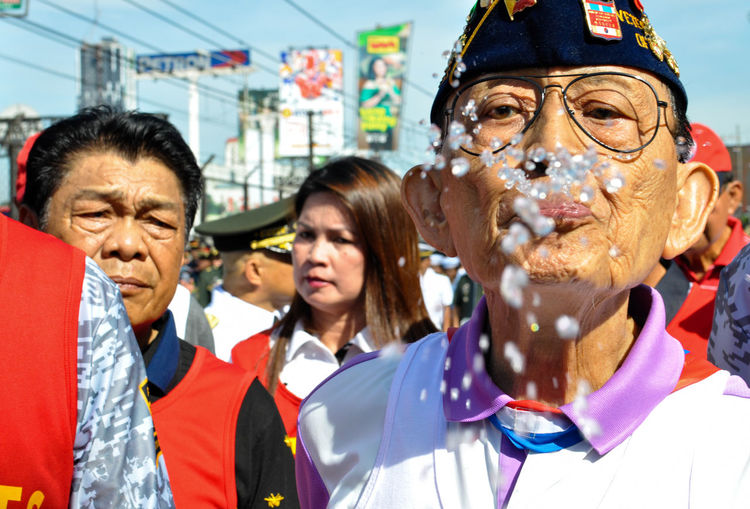 an Iconic and historical character gone wrong. Former Philippine President and EDSA Revolution iconic figure Fidel V. Ramos spits water to the group of photographers during the commemoration of the 32nd EDSA Revolution Anniversary February 25, 2018. No one knows why he does the spitting. It is uncertain whether former Philippine President was being playfull or not when he spat at group of media and photographers. This is why i love the vision that a photo reveal. Historically amusing and sociologically fascinating. Spitting Water City Women Group Of People Portrait Men Senior Adult Crowd The Street Photographer - 2018 EyeEm Awards The Photojournalist - 2018 EyeEm Awards The Troublemakers Streetwise Photography