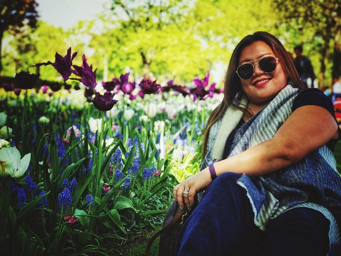A lady poses for a portrait sat down in a garden. Sat Down Outdoors Flowers Beautiful Garden Plant Sunglasses Flower Glasses Lifestyles Leisure Activity Real People Flowering Plant Young Adult One Person Growth Adult Smiling Three Quarter Length Women Young Women Looking At Camera Beauty In Nature Portrait Fashion