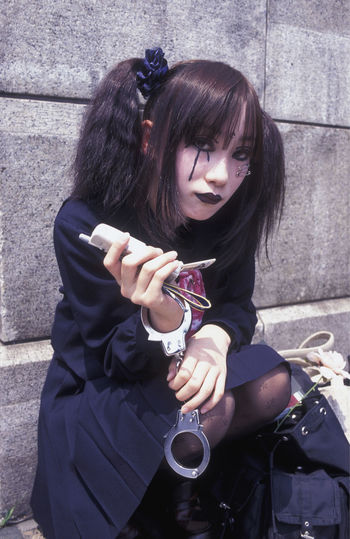 Young Woman Wearing Make-Up With Handcuffs Holding Phone While Sitting On Steps