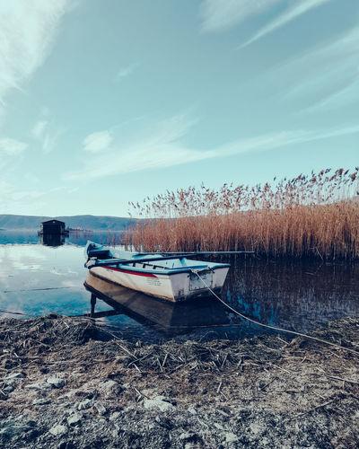 Boat moored on shore against sky
