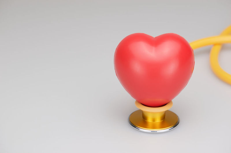 Red heart on yellow and gold stethoscope with white background. Care Curve Doctor  Gold Red Shape Therapy Background Cardio Copy Space Equipment Health Heart Medical Stethoscope  Tool Treatment White