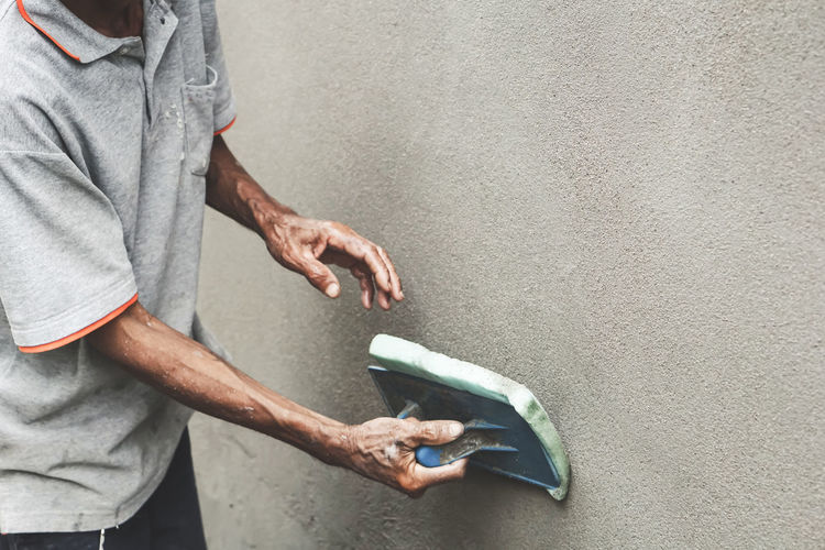 Asian male worker plasterer using a plastering sponge float on an outdoor cement wall