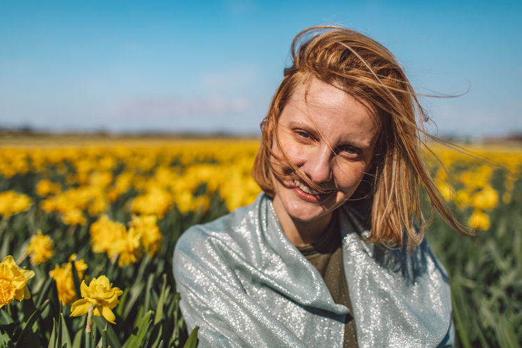 Portrait of woman with yellow flowers in field