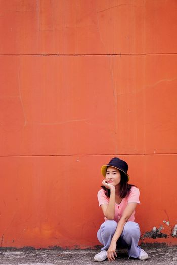 Woman looking away while sitting against orange wall