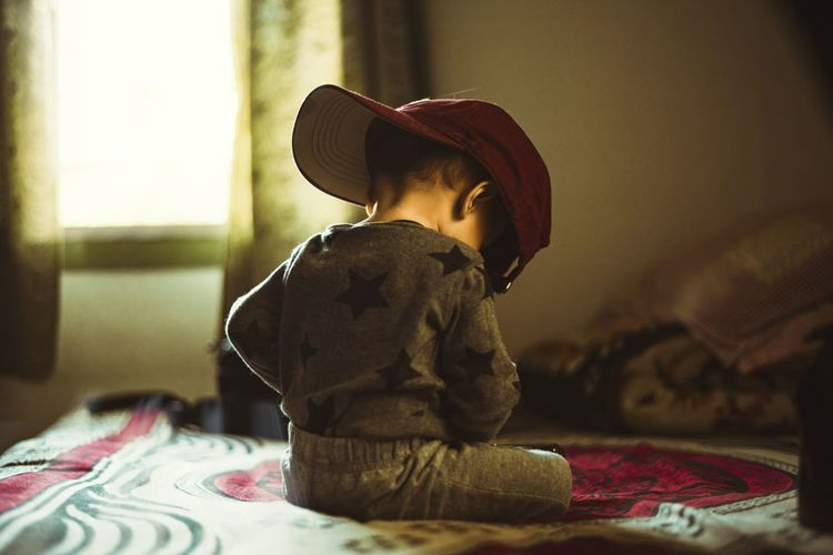 Boy sitting on bed at home
