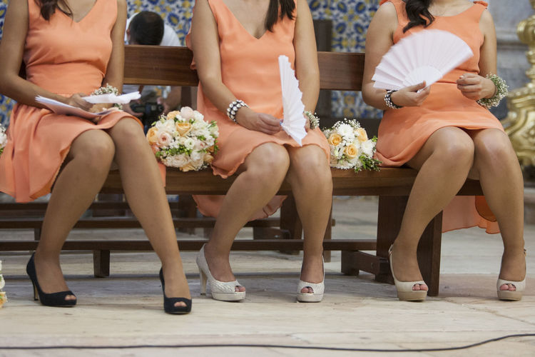 Low section of bridesmaids sitting on bench