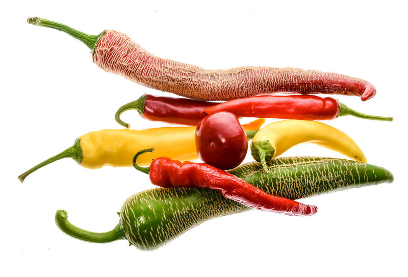 Red hot chili peppers Cayenne, Serrano with green stem. Cayenne, Serrano or Sicilian variety of chili. Studio image Isolated on white background. Capsicum Annuum Cayenne Pepper Cherry Chili Pepper Green Hot Hot Pepper Macedonian Fringed Red Bunch Capsaicin Capsicum Chinense Capsicum Pepper Chilli Close-up Food Fresh Fringed Homegrown Jalapeno Pepper Macedonian Studio Shot Vegetable White Background Yellow