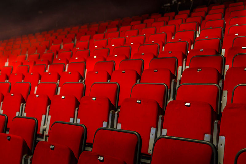 Low angle view of empty red chairs in movie theater