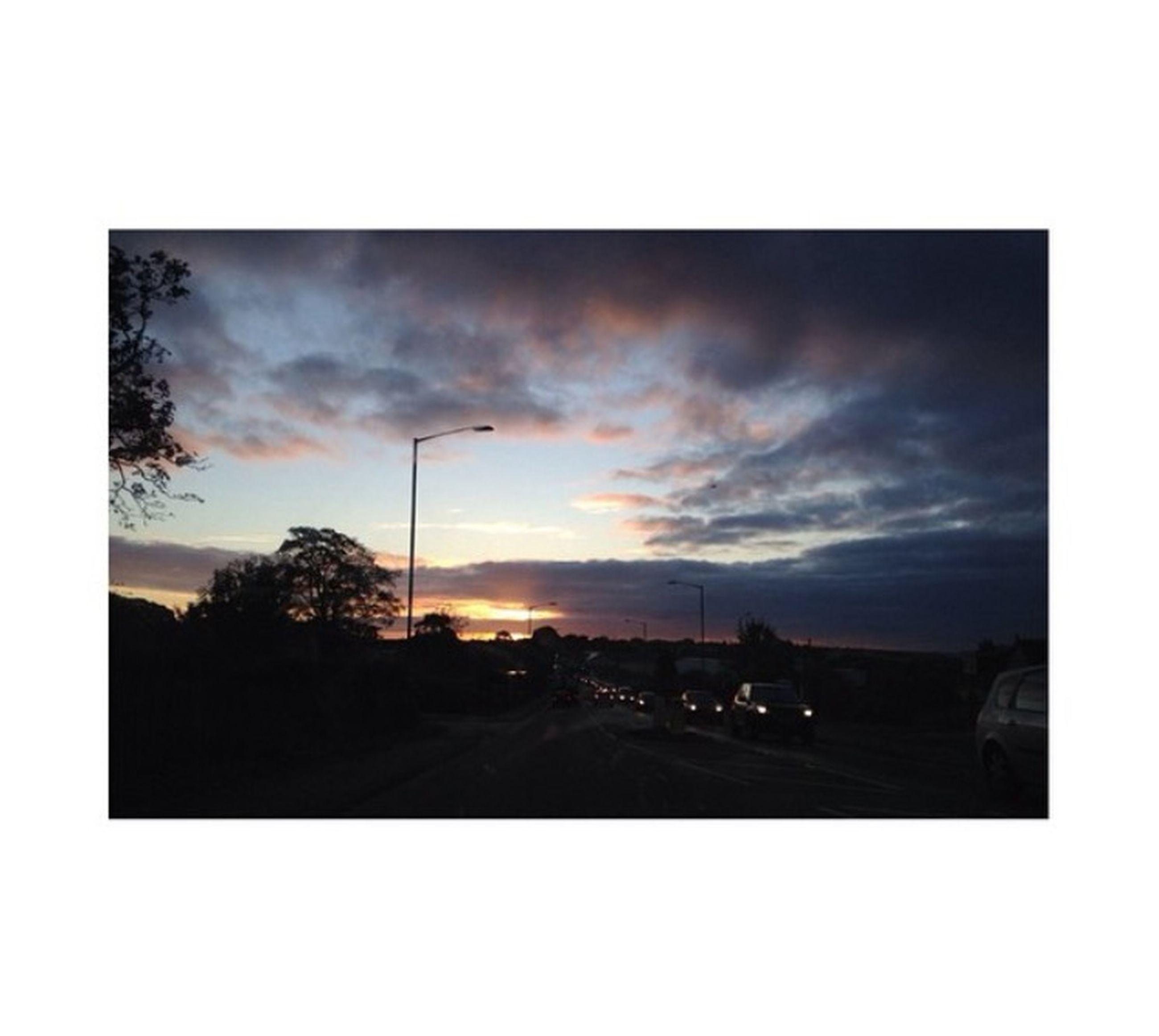 sunset, sky, silhouette, transportation, car, transfer print, cloud - sky, road, land vehicle, auto post production filter, building exterior, street, street light, built structure, mode of transport, cloud, cloudy, tree, nature, dusk