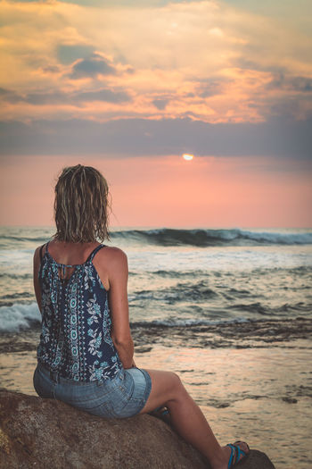 Woman sitting on rock at beach against sky during sunset