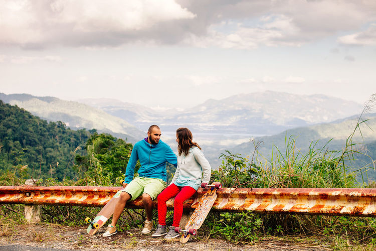 Couple Sitting On Fence Against Cloudy Sky