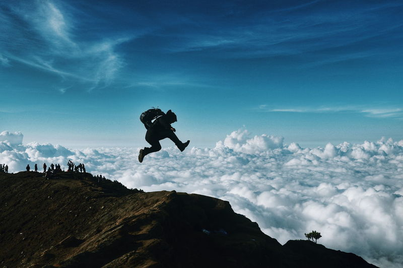 Man jumping on top of mountain against sky