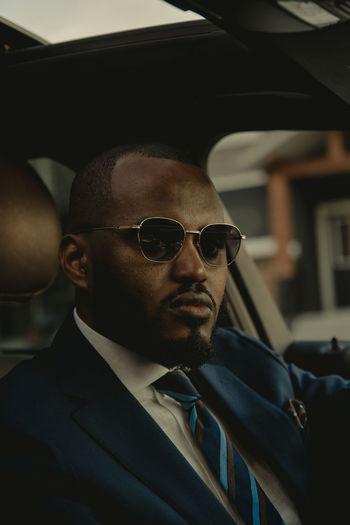 Portrait of man wearing sunglasses in car