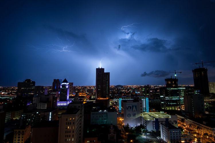 Lightning Over Illuminated Buildings In City At Night