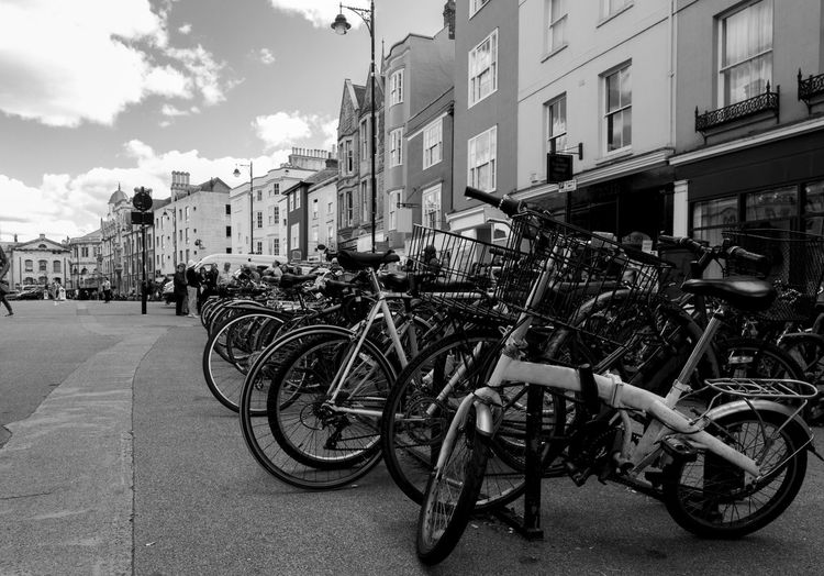 Bicycles parked on street in city against sky