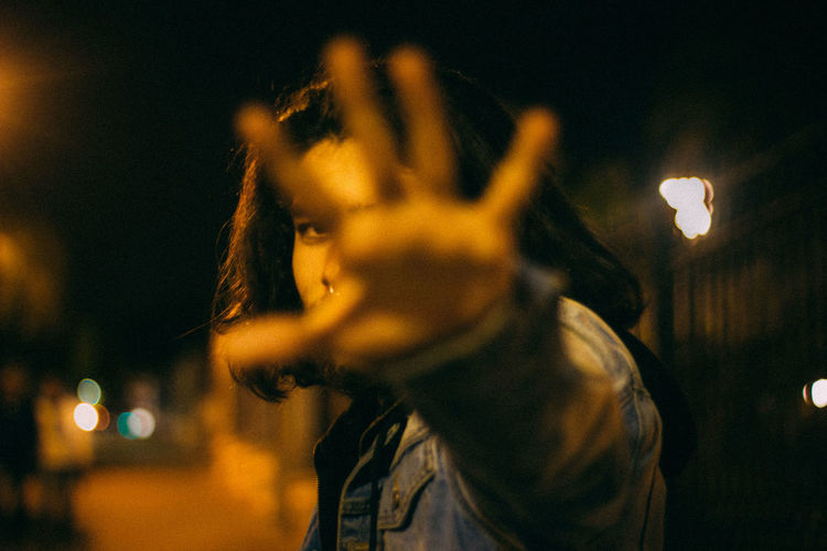 Portrait of man gesturing outdoors at night