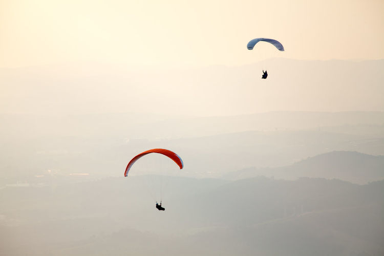 People Paragliding Against Sky During Sunset
