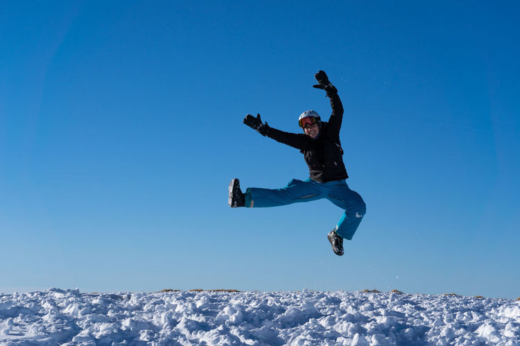 Full length of man jumping against clear blue sky