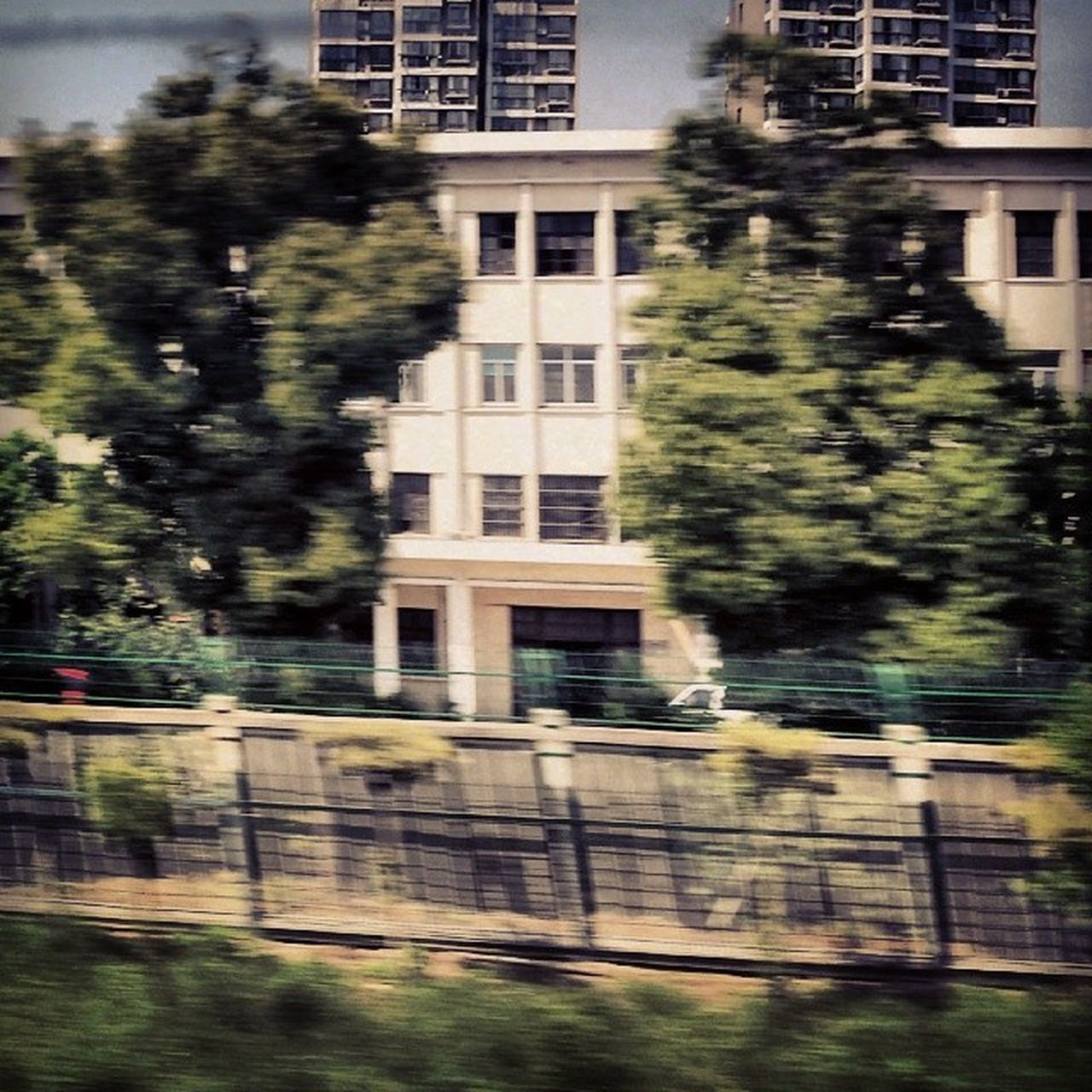 architecture, building exterior, built structure, tree, blurred motion, no people, day, city, outdoors, motion, nature, sky