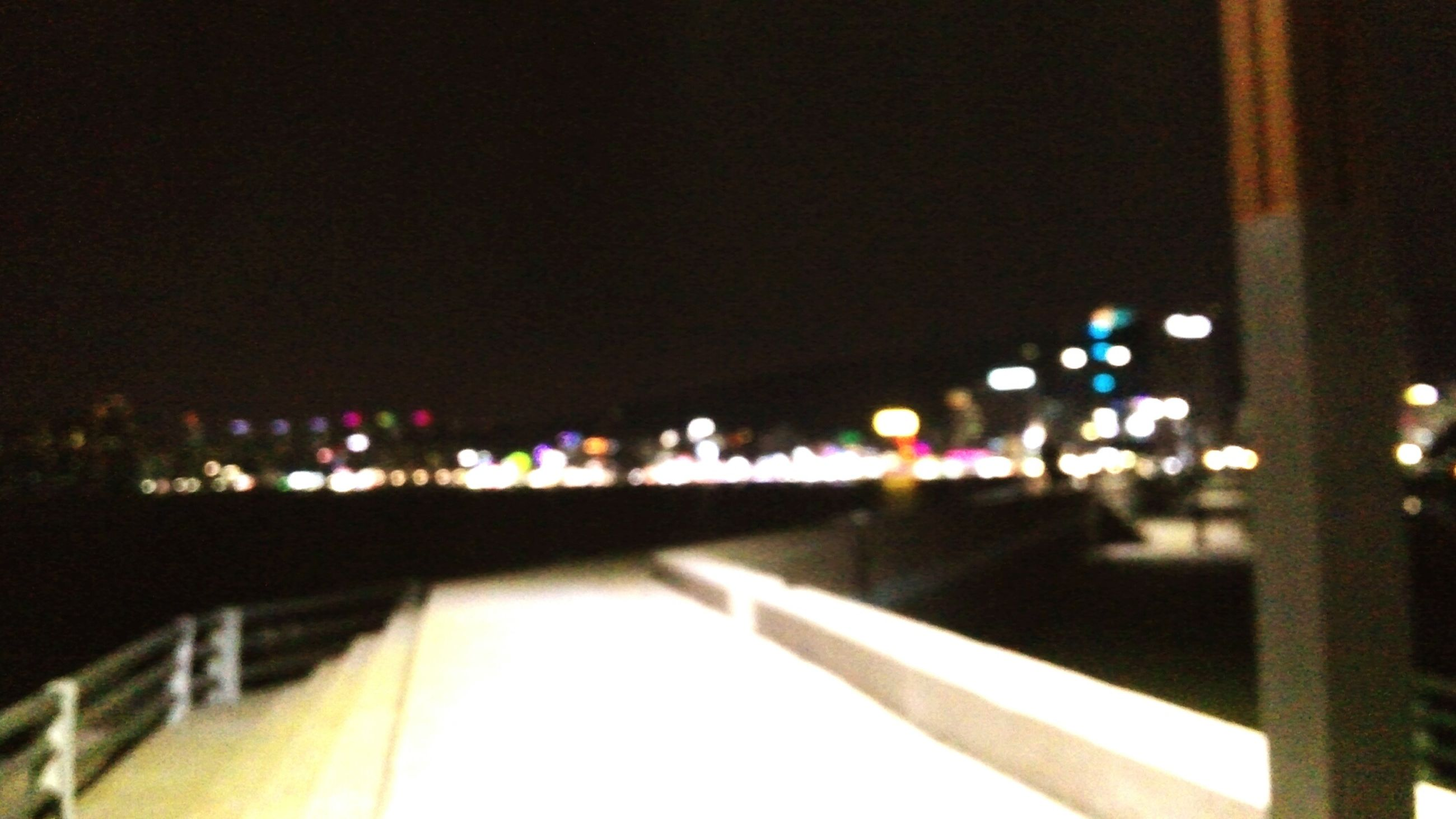 illuminated, night, lighting equipment, architecture, built structure, city, street light, railing, building exterior, light - natural phenomenon, copy space, clear sky, no people, dark, defocused, electric light, outdoors, light, focus on foreground