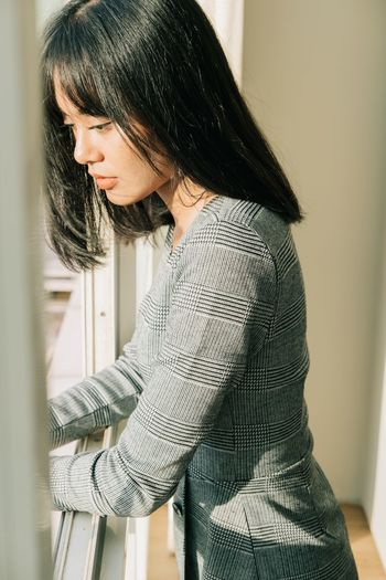 Side view of young woman looking at home