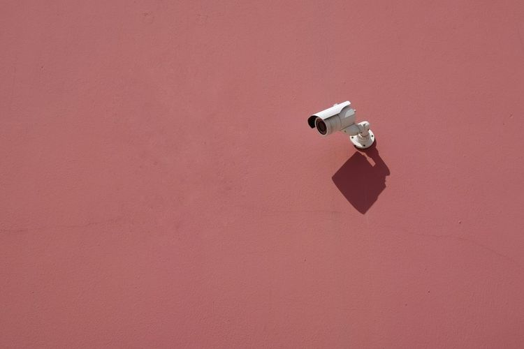 Low Angle View Of Security Camera On Red Wall