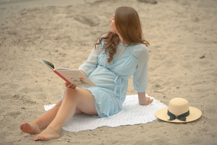 Young woman using mobile phone while sitting on beach