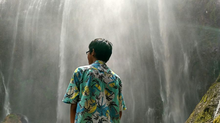 Rear view of man standing against waterfall