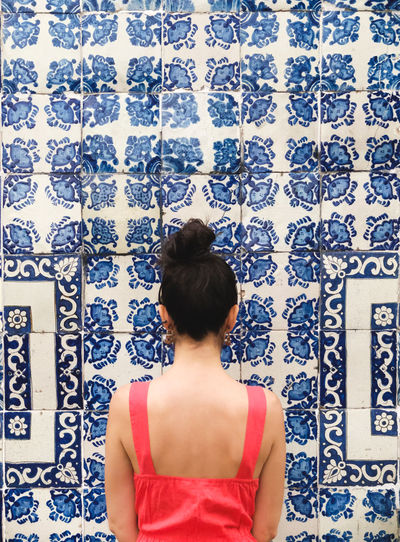 Rear view of woman standing against patterned blue tiled wall