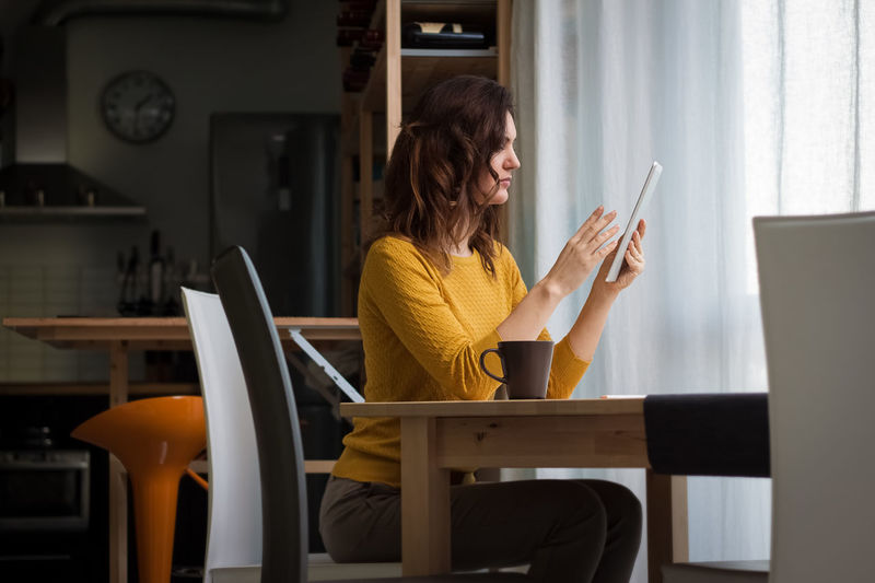 Brunette woman using tablet, not facing camera Sitting One Person Adult Indoors  Table Chair Women Wireless Technology Young Adult Communication Seat Holding Casual Clothing Computer Three Quarter Length Real People Home Interior Lifestyles Tablet Working From Home Freelance Life Freelancing Freelance Creative Brunette