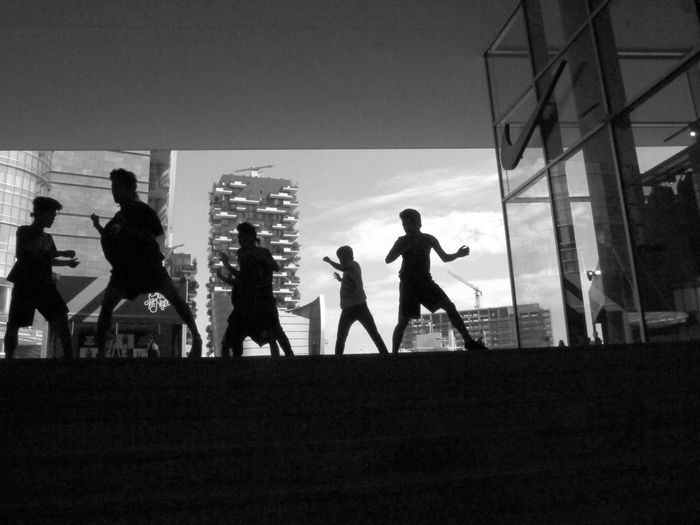 Silhouette boys dancing with buildings in background