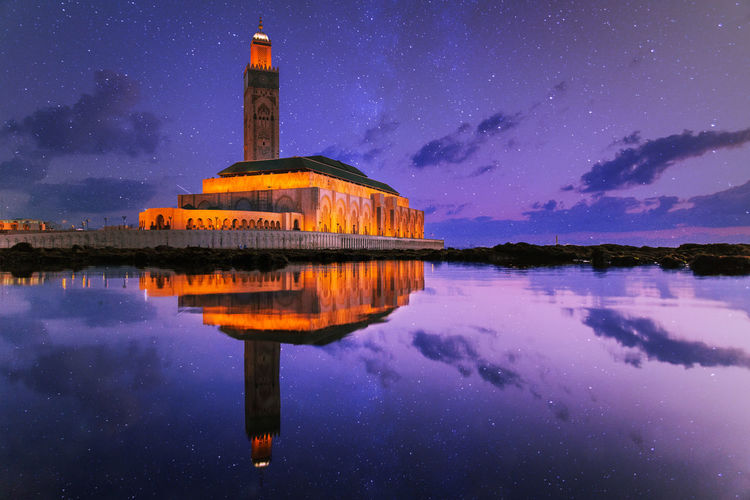 Reflection of illuminated historic mosque on sea against star field