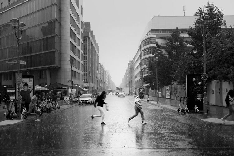 People walking on wet street in rainy season