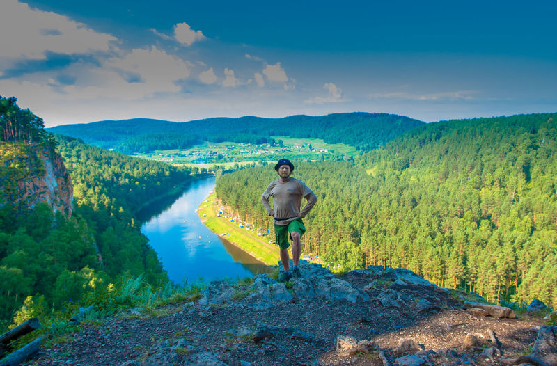 Man standing on mountain against river in forest