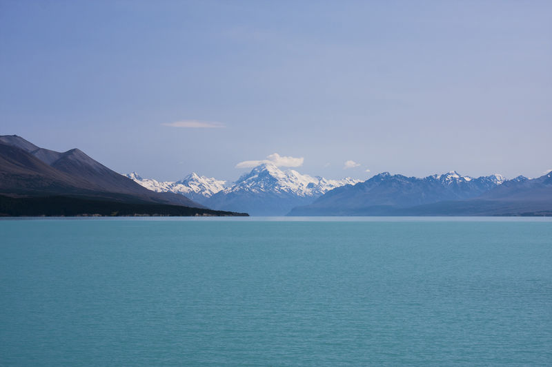 Scenic view of sea and snowcapped mountains against blue sky