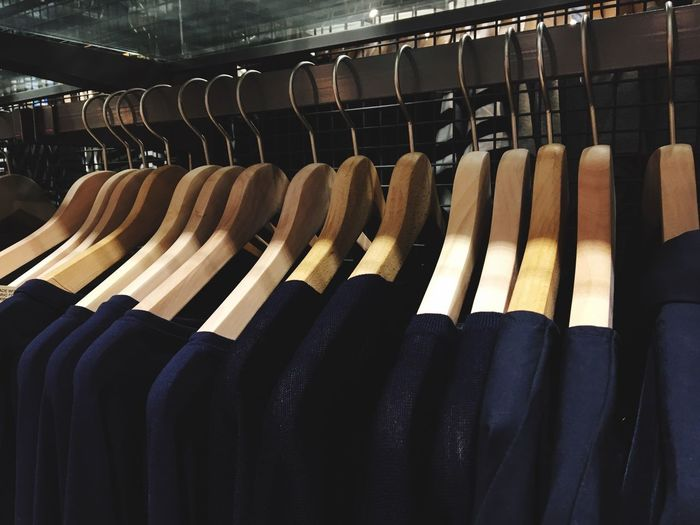Close-up of clothes hanging in row on coathangers at shop