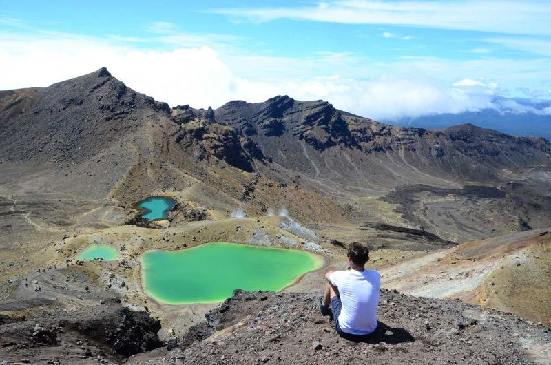 Rear View Of Man Sitting On Rock Against Sky At Tongariro National Park