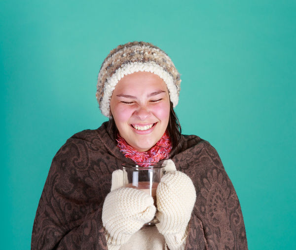 Portrait Of Teenage Girl In Warm Clothing Having Drink Against Green Background