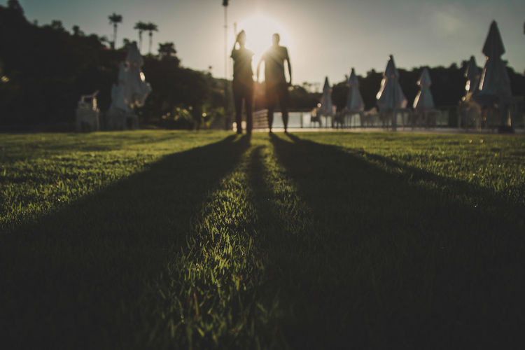 Surface level of silhouette man and woman standing on field