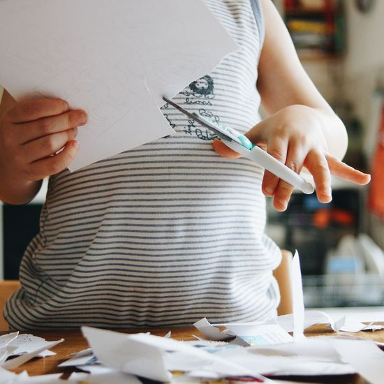 Midsection of child cutting papers on table while standing at home