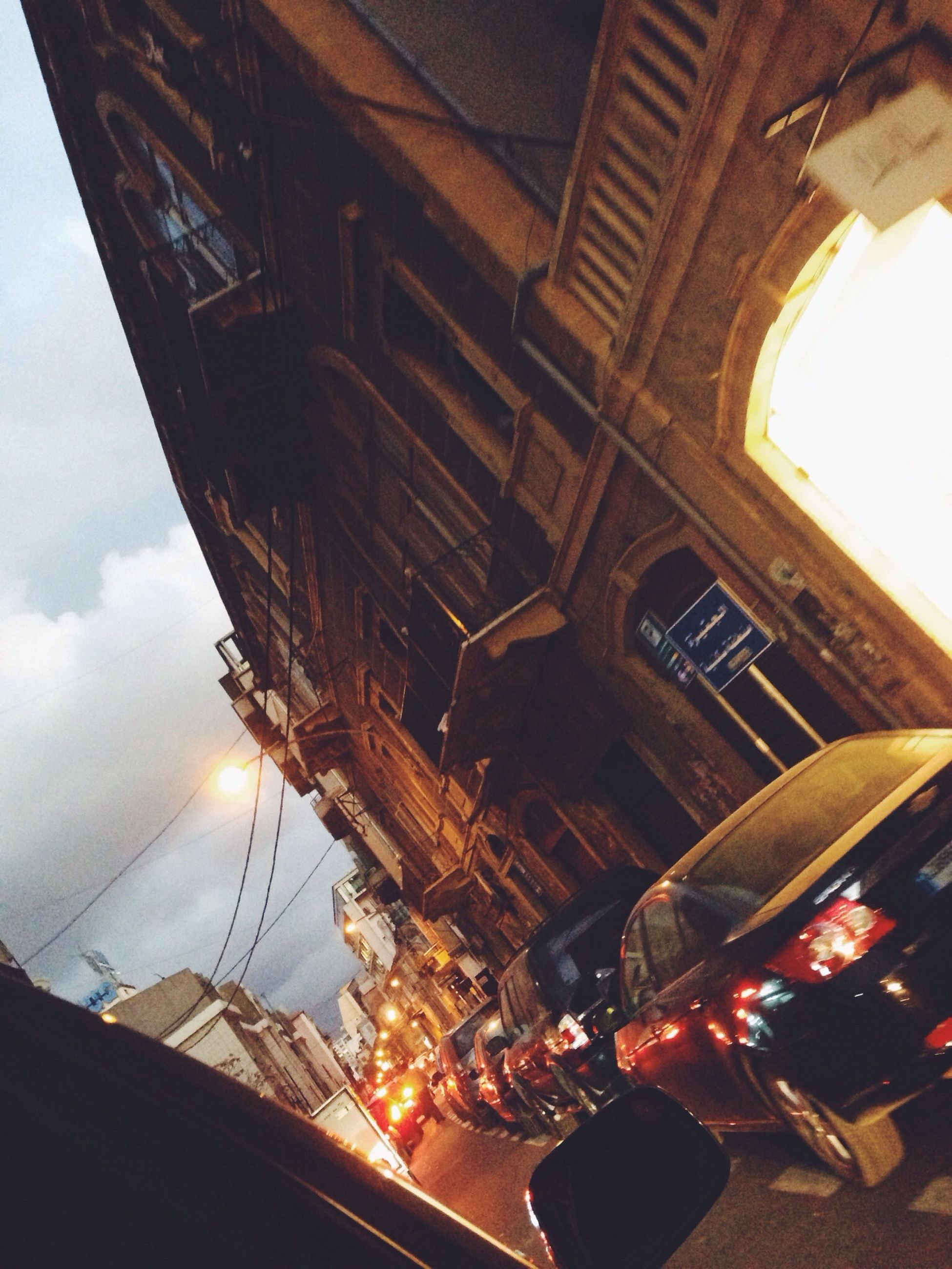 architecture, built structure, building exterior, low angle view, sky, transportation, city, mode of transport, building, illuminated, car, travel, cloud - sky, arch, outdoors, reflection, bridge - man made structure, dusk, window, connection